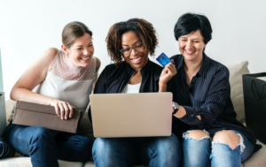 three woman looking at the laptop and holding a card